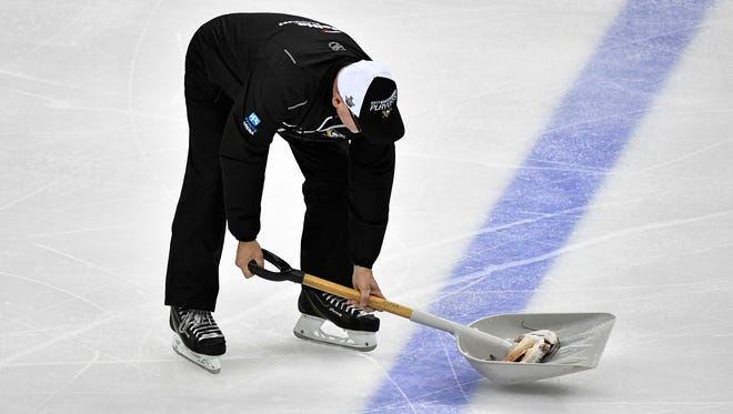 A catfish is scooped off the ice after a fan threw it during the second period of Game 1 of the Stanley Cup Final at PPG Paints Arena  on Monday, May 29, 2017.