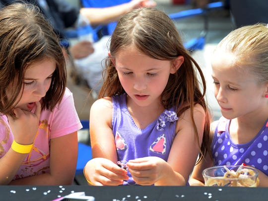 Carmella Friel (left) of Smyrna and her friends River Cordeiro, 7, and Catherine Hornberger, 6, located a children's jewelry vendor at the festival.