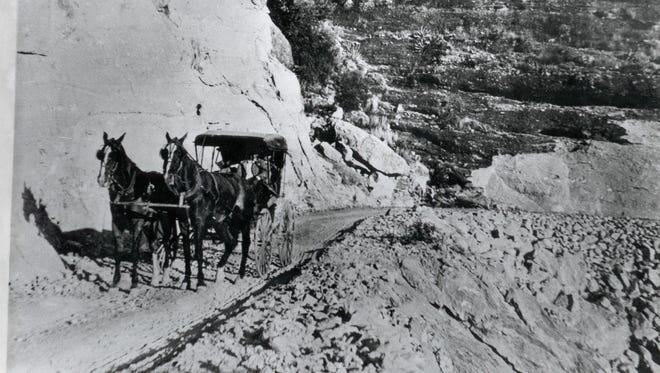 THEN: A horse and carriage travel along the Apache Trail at Fish Creek Hill. The date of the photo is unknown.