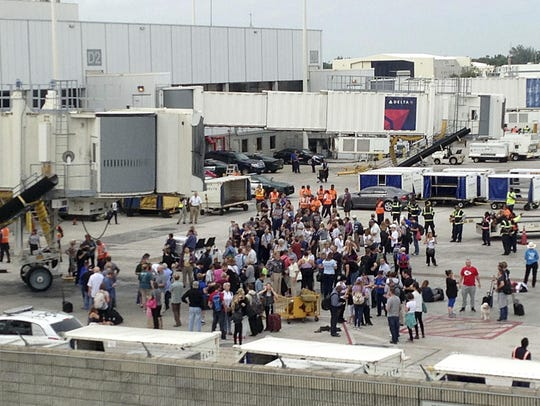 People stand on the tarmac at the Fort Lauderdale-Hollywood