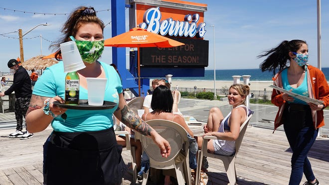 Shannon Svenson, a server at Bernie's Beach Bar at Hampton Beach brings a Corona with a lime to a customer, as outdoor decks at the beach began to reopen June 4.