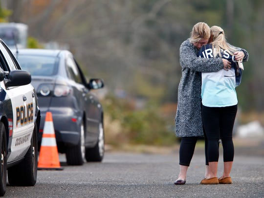 A woman who police identified as a friend of the victim is consoled by another woman on the long driveway that leads to the rear of the Froggia Florist and Greenhouses in Oceanport, NJ, where the body of Joseph Comunale, a 26-year-old Hofstra University graduate originally from Connecticut, was reportedly found Wednesday, November 16, 2016.