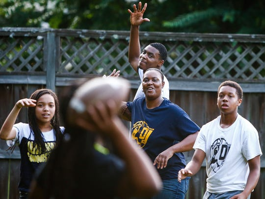 Team Penny standout D.J. Jeffries (top) plays football with his mother, Shatonya Hardaway (middle bottom), and family members at their home in Olive Branch, Miss.