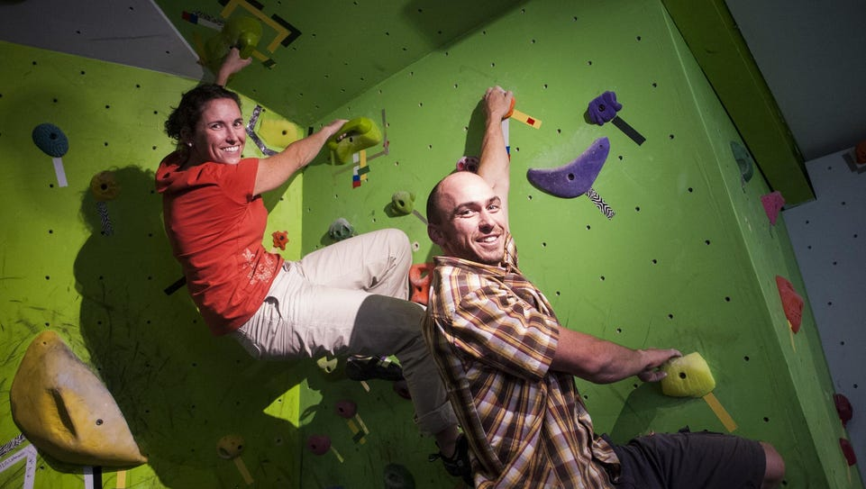 Abby and Brian Thompson hang from holds in Hi-Line
