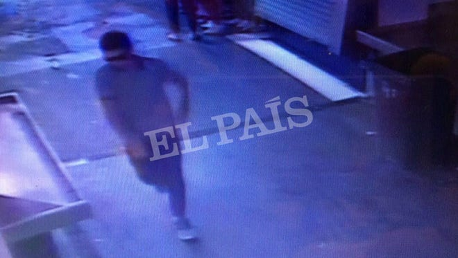 In this watermarked frame grab from CCTV released by the Spanish newspaper 'El Pais' on Monday Aug. 21, 2017, a suspect believed to be Younes Abouyaaqoubis is captured by a security camera walking through La Boqueria market seconds after a van crashed into pedestrians in Barcelona Aug. 17.