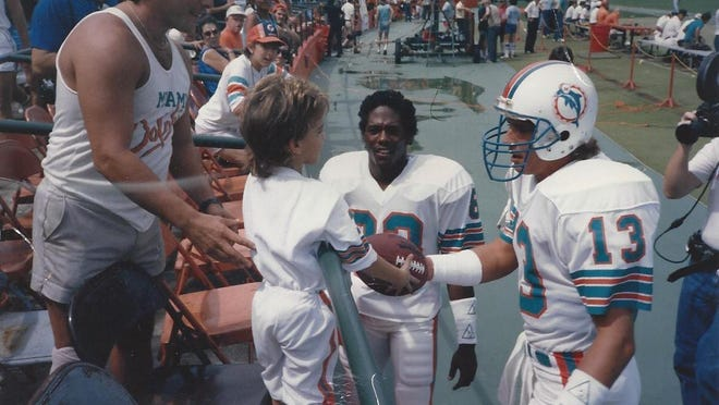 Gary Baumwoll receives a football from Dan Marino in 1985, a moment captured by NFL Films.