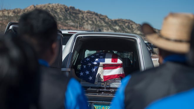 In this March 16, 2017, photo, family members of fallen Navajo Nation police officer Houston Largo wear blue in his honor and stand by to wait for his casket to be removed from the hearse during funeral services in Gallup, N.M. Largo, a Navajo Nation police officer, was shot while responding to a domestic violence call in remote New Mexico. Investigators say the man accused of killing Largo had spent the afternoon drinking and was intoxicated the night of the shooting.