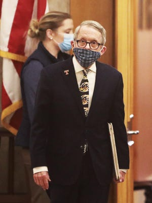 Ohio Gov. Mike DeWine, wearing an Akron Rubber Ducks tie, walks into the daily coronavirus news conference on Friday, April 17, 2020 at the Ohio Statehouse in Columbus, Ohio.