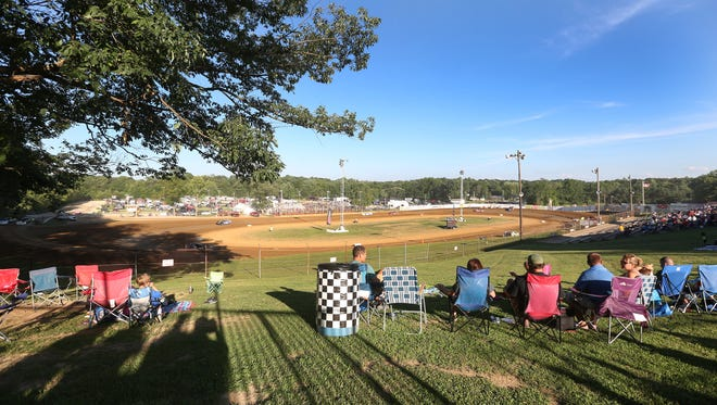 Fans sit in the grassy lawn area off of turn three at Lincoln Park Speedway in Putnamville, July 1, 2016.