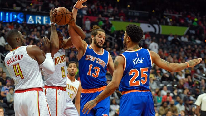 New York Knicks center Joakim Noah (13) and Atlanta Hawks center Dwight Howard (8) get tied up fighting for a rebound during the first half at Philips Arena.