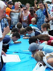 Participants give it their all during the pie eating contest.