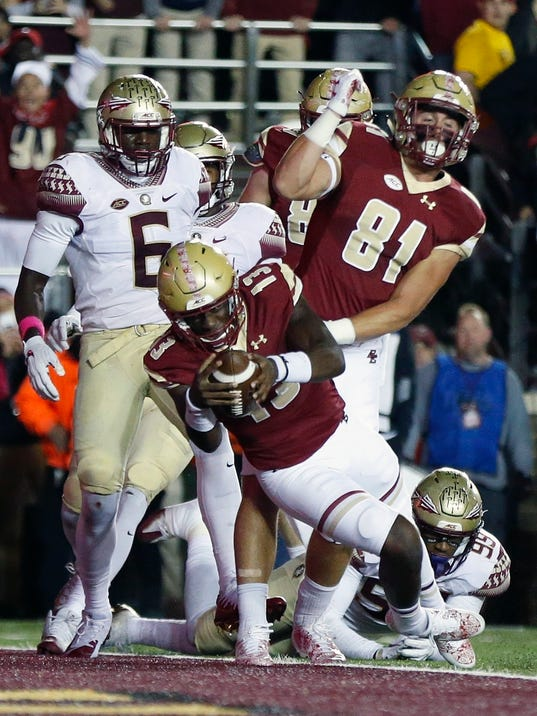 Boston College quarterback Anthony Brown (13) scores in front of Florida State linebacker Matthew Thomas (6) during the half of an NCAA college football game in Boston, Friday, Oct. 27, 2017. (AP Photo/Michael Dwyer)