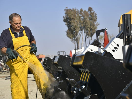 Bobby Mahaffey owner of Mahaffey Steam Cleaning cleans ag equipment that will soon be showcased in the 51st World Ag Expo.