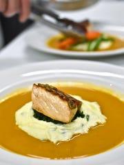 Chef Josh Krechel plates Pepita-crusted seared salmon at Starry Night Cafe in Ferrisburgh.