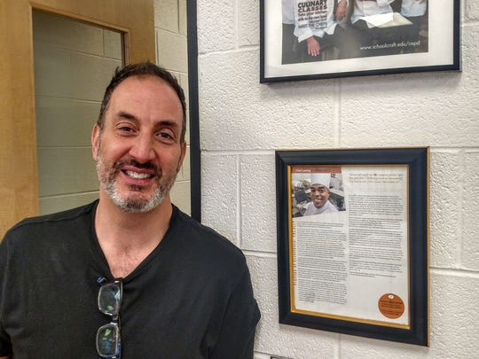 Chef Sam Musto stands next to a display featuring several Schoolcraft College chefs hanging in a classroom at Saline High School.