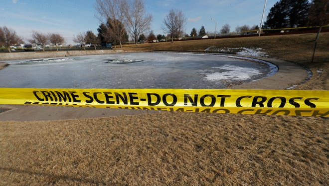 A rope of crime tape is shown around a small, ice-covered lake Tuesday, Jan. 3, 2017, in Aurora, Colo. Divers looking for a 6-year-old boy who apparently wandered away from his family's home on New Year's Eve found his body in the lake Tuesday.