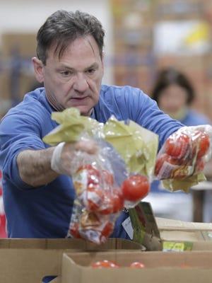 Volunteer Jeff Ellis unloads tomatoes while working last week at the St. Joseph Food Program in Menasha. Wm. Glasheen/USA TODAY NETWORK-Wisconsin.