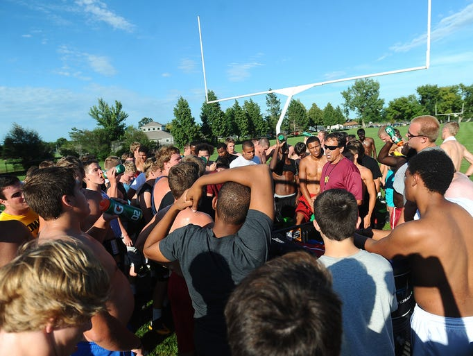 Roosevelt's head football coach Kim Nelson gives his team a pep talk after football practice at Roosevelt High School on August 25, 2014.
