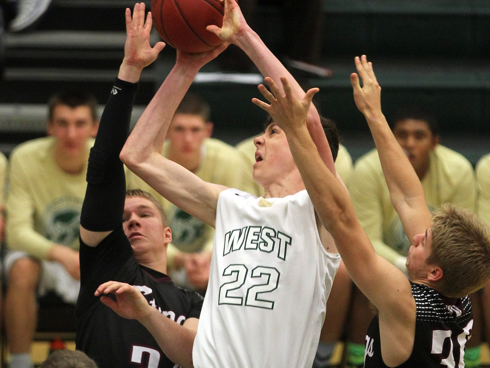 West High's Patrick McCaffery draws a foul as he takes a shot during the Trojans' game against Mount Vernon on Thursday, Dec. 3, 2015.