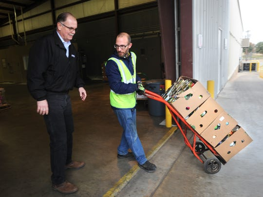 "James Oliver, center, and Philip Grice, right, unload 12,458 pounds of food raised by the CityLink ""Food for Fares"" fundraiser to the Food Bank of West Central Texas."