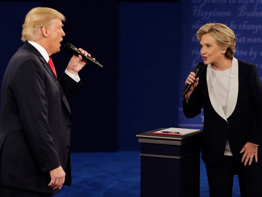In this Sunday, Oct. 9, 2016, file photo, Republican presidential nominee Donald Trump and Democratic presidential nominee Hillary Clinton speak during the second presidential debate at Washington University in St. Louis. Trump's presidential transition team on Saturday, Dec. 10, 2016, challenged the veracity of U.S. intelligence assessments that Russia was trying to tip the November election to the Republican. A top Senate Democrat demanded a full congressional investigation.