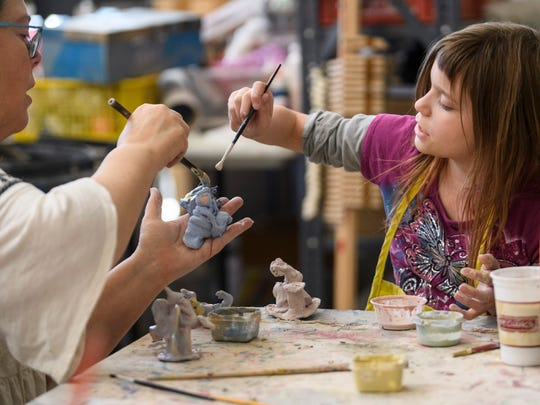 Jane Case Vickers and Eliza Shirel, 9, work together as they glaze fairy figurines before putting them into the kiln at Patchwork Central in Evansville, Ind., Tuesday, April 17, 2018.