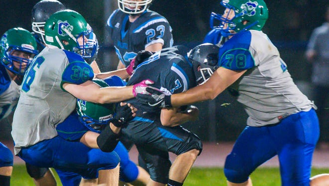 Colchester's Stephen Emmons, left, and Russell Chase, right, tackles South Burlington's Ryan Tarte in Colchester on Friday, September 8, 2017.