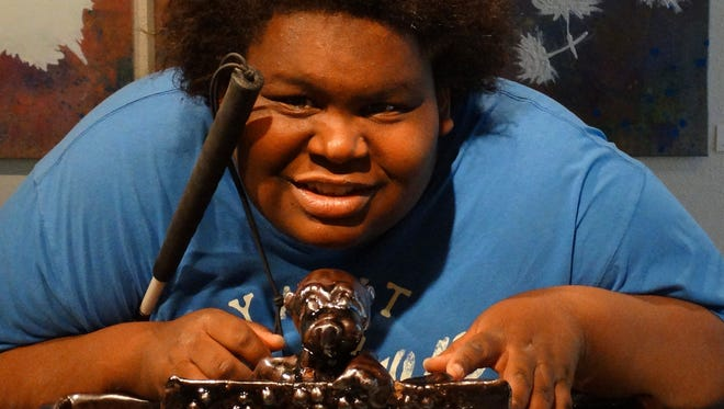 Lavon Smith, 17, poses with this piece of artwork that he produced in a class at New Mexico State University-Alamogordo. It is the center piece of a display at the University. Smith has been blind since the age of 6.