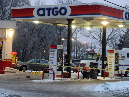 Evidence markers litter the lot outside a Citgo gas