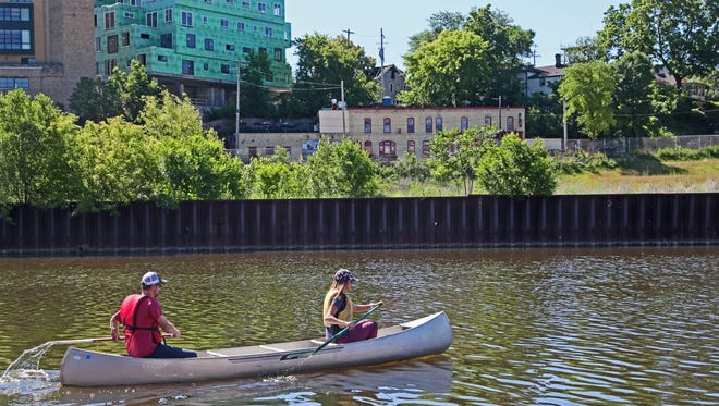 Todd Engen, left, and Jennifer Ward paddle a canoe borrowed from the Urban Ecology Center on the Milwaukee River in 2018.