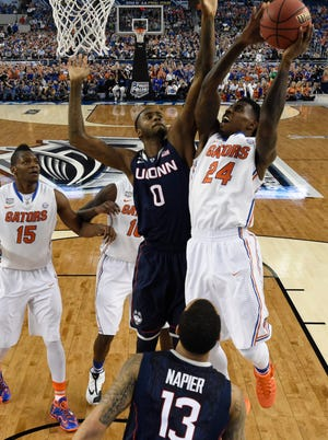 Florida Gators forward Casey Prather (24) shoots the ball while defended by Connecticut Huskies forward Phillip Nolan (0).