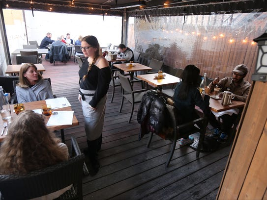 Server Beth Fisher waits on tables in the outdoor seating