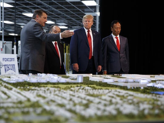 In this June 28, 2018 photo, President Donald Trump takes a tour of Foxconn with Foxconn chairman Terry Gou, right, and CEO of SoftBank Masayoshi Son in Mt. Pleasant, Wis.