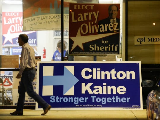 A man walks past a Clinton/Kaine sign outside the Nueces County Courthouse in Corpus Christi.