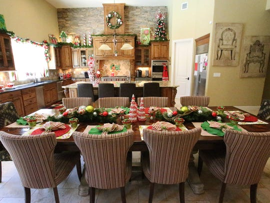 The kitchen and dining table at the Hughes home are laid out in Christmas colors.
