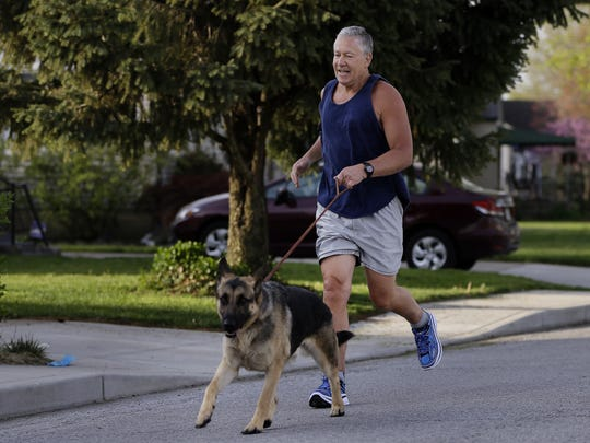 John Miller takes a run along the street of his Speedway home on April 19, 2016. His running partner and dog Zeke, a two-year-old German Shepherd, tags along.