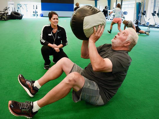 Personal trainer Kim Swenson works with Jeff Reed Friday,