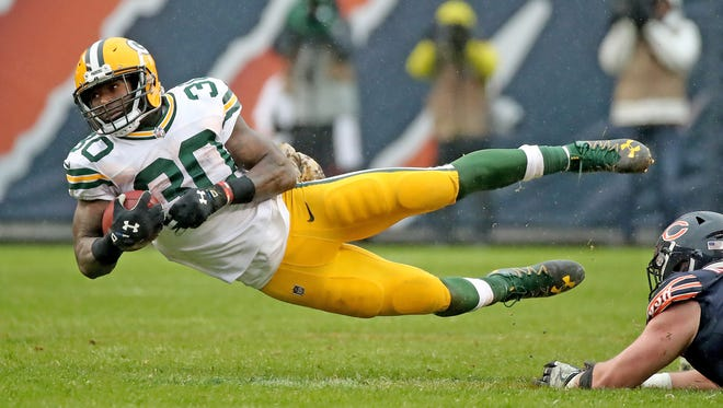 Green Bay Packers running back Jamaal Williams (30) dives through a hole for a first down on fourth and 1 against the Chicago Bears Sunday, November 12, 2017 at Soldier Field in Chicago, Il.
