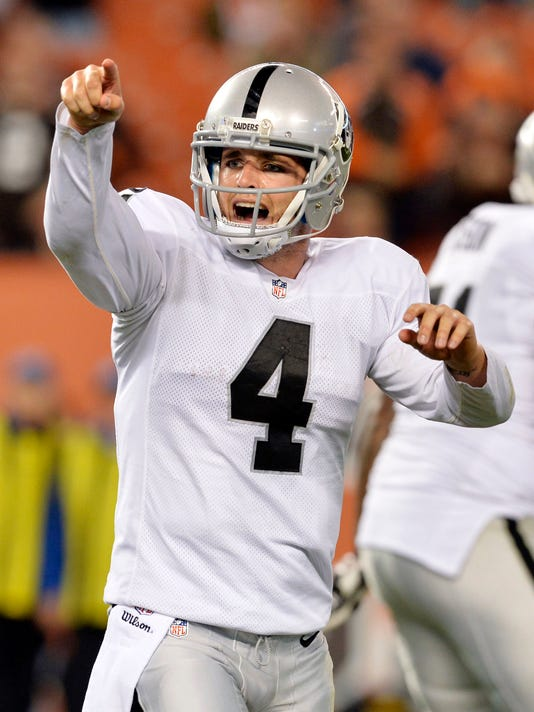 Oakland Raiders quarterback Derek Carr reacts after throwing a touchdown pass to wide receiver Andre Holmes in the fourth quarter of an NFL football game against the Cleveland Browns, Sunday, Oct. 26, 2014, in Cleveland. (AP Photo/David Richard)