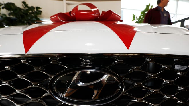 A buyer looks over a 2018 Sonata on the showroom floor of a Hyundai dealership in Littleton, Colo. Insurance might be the least exciting thing about surprising your loved one with a valuable gift this holiday, but don't let it fall off your priority list. If your gift involves four wheels and a big red bow, the person driving it will need his or her own insurance, and you'll need coverage to get it off the lot.
