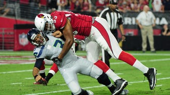 Arizona Cardinals defensive end Calais Campbell (93) tackles Seattle Seahawks quarterback Russell Wilson (3) during the first half at University of Phoenix Stadium.