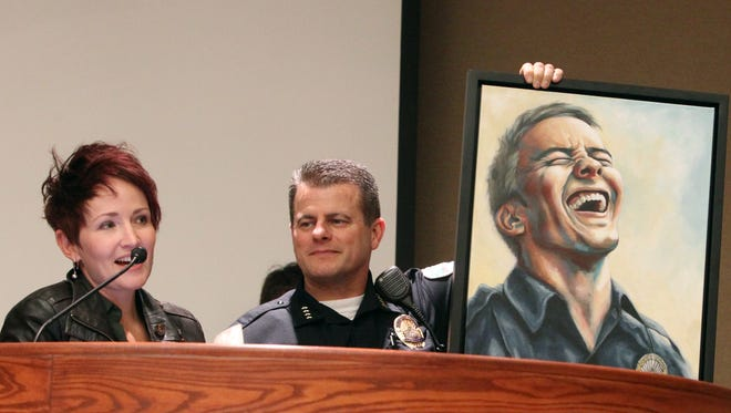 Artist Nicola Hill, left, speaks Tuesday night after presenting Redding Police Chief Roger Moore with a painting of a smiling police officer, which accompanied a donation from Bethel Church to the city of $25,000 to buy police drones.
