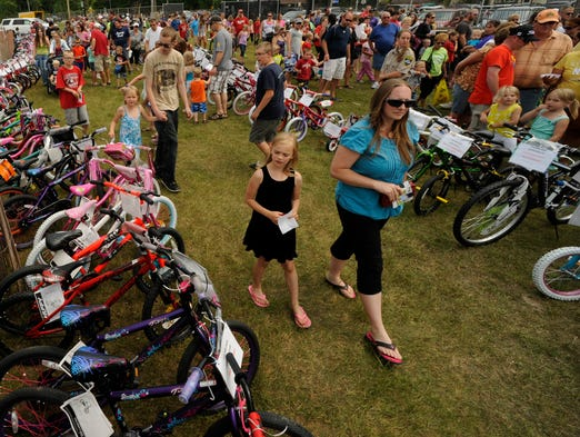 Hundreds pack Walsh Field as children and parents look at the 154 bicycles being given away during the 36th annual Two Rivers Fish Derby & Festival on Saturday, July 19, 2014 in Two Rivers. Matthew Apgar/HTR Media