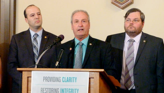Michigan state Rep. Joe Graves, R-Argentine Township, helps unveil bipartisan legislation to improve the state's unemployment benefits system on Thursday, Oct. 19, 2017, at the Capitol in Lansing. Also pictured are Rep. Kevin Hertel, left, D-St. Clair Shores and Rep. Phil Phelps, D-Flushing.