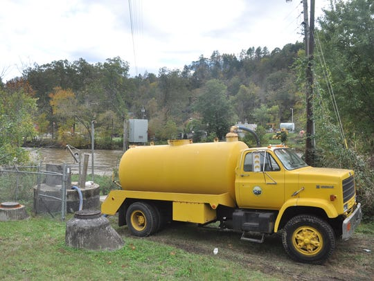 Maintenance personnel from Marshall use a 3,000-gallon sewer pump truck from Mars Hill to collect wastewater from a lift station beside the French Broad River. A broken pipe beneath the river sent an estimated 100,000 gallons into the river, according to two officials.