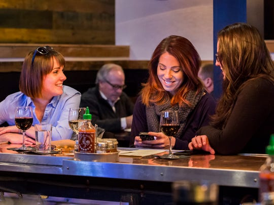 Erin Duckes (left), Emily Riley (center) and Alex Chameney (right) hang out at the bar at the Eighth & Union Kitchen on Wednesday night.