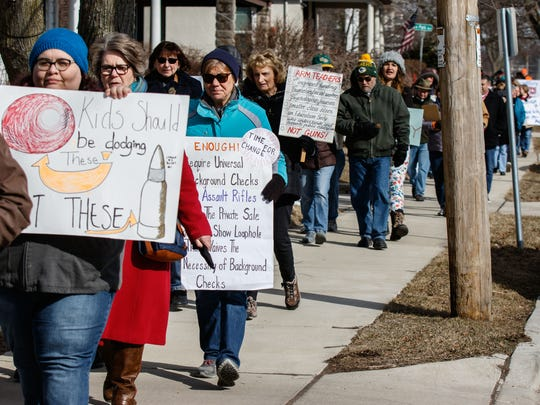 Members of the community from the Waukesha School District march down Maple Ave. toward district headquarters during a gathering to show support for students participating in the National School Walkout.