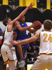 Reed's Matthew Williams (33) gets fouled by Galena's Moses Wood (11) while driving to the basket during their basketball game at Galena on Feb. 14, 2018.