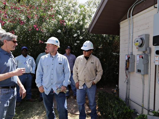 The residential design manager of American Solar and Roofing, Chuck Adams, left, in blue with no hard hat, talks to with SRP engineers, Joel Dickenson, center, and Ernie Tom about the interface between the power grid and a new solar power inverter that just installed at a Phoenix home.