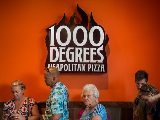 Customers wait in line to order their customizable pizzas at 1000 Degrees Neapolitan Pizza in Turkey Creek on Thursday, July 6, 2017.